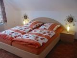 Schlafzimmer mit Doppelbett und Einzelbett. Zusätzlich ist ein Kinderbett vorhanden.