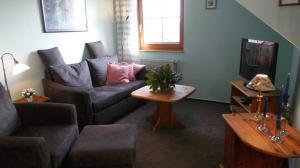 SAT - TV - Ecke, Sofa, Sessel mit Fußhocker.
